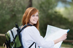Young woman backpacking in nature. With a rucksack on her back and a topographical map in her hands Stock Photos