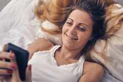 Young woman in bad looking at her phone Royalty Free Stock Photos