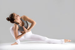 Young woman in Baddha Ardha Samakonasana pose, grey studio backg Royalty Free Stock Images