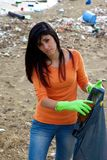 Young woman with bag full of dirt on destroyed dirty beach Stock Photography