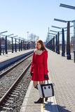Young woman with bag at a train station Stock Images