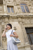 Young woman with bag using mobile phone outdoors, smiling, low angle view Royalty Free Stock Images