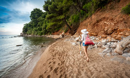 Young woman with bag walking on deserted sea shore Royalty Free Stock Image