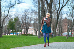 Young woman with bag walking in park Royalty Free Stock Photos