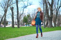 Young woman with bag walking in park Stock Photography