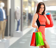 Young woman with bags in shopping mall Stock Photo