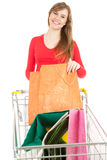 Young woman with bags and shopping  trolley Royalty Free Stock Photo