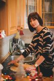Young woman baking christmas cookies at the decorated kitchen Stock Photos