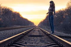 Young woman balance on railroad in sunset beams Royalty Free Stock Images