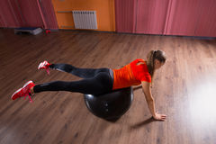 Young Woman Balancing on Exercise Ball in Studio Royalty Free Stock Photos
