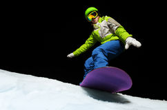 Young woman balancing with hands on snowboard. Portrait of young woman wearing ski mask balancing with hands on snowboard and ready to slide down at night Stock Photo
