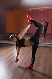 Young Woman Balancing on One Leg in Dance Studio Royalty Free Stock Photography