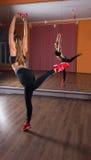 Young Woman Balancing on One Leg in Dance Studio Stock Image