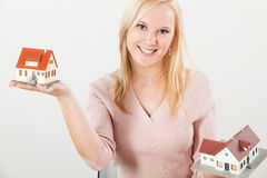 Young woman balancing two houses with hands Stock Photography