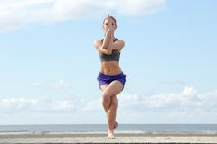 Young woman balancing in yoga position. At the beach Royalty Free Stock Photos