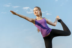 Young woman in a balancing yoga position. Young beautiful woman in a balancing yoga position Royalty Free Stock Photo