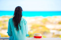 Young woman on balcony with view on a tropical beach Stock Images