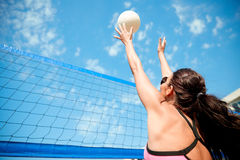 Young woman with ball playing volleyball on beach Stock Photography