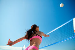 Young woman with ball playing volleyball on beach Stock Photo