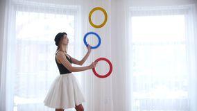 Young woman ballerina juggling with a circle things. Mid shot stock video