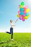 Young woman with balloons in hands in the field against the sky Royalty Free Stock Photography