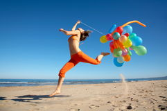Young woman with balloons jumping. Young woman with different colored balloons jumping on the beach royalty free stock photo