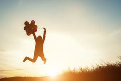Young woman with balloons jumping outdoor royalty free stock photo