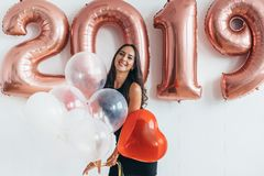 Young woman with balloons posing celebrating New Year Stock Photo