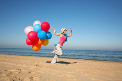 Young woman with balloons running on the beach. Young woman with different colored balloons running on the beach Royalty Free Stock Photo