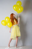 Young woman with balloons. Young woman in a yellow dress with balloons Royalty Free Stock Photography