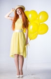 Young woman with balloons. Young woman in a yellow dress with balloons Royalty Free Stock Photos