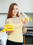 Young woman with bananas in  kitchen Royalty Free Stock Photography
