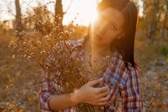 Young Woman With Banch Of Wildflowers In Her Hands Backlit. Vintage Color Image Royalty Free Stock Images