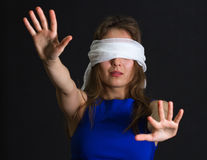 Young woman bandage on eyes. Concept of uncertainty, blindness or helplessness: portrait of young lost woman (girl) with white bandage on eyes and arms Royalty Free Stock Photography