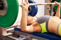 Young woman with barbells�bench pressing weights Royalty Free Stock Photo