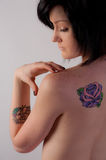 Young Woman with Bare Back and Tattoo. A simple portrait of a dark haired young woman with a flower tattoo on her bare back and another tattoo on her forearm stock image