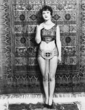 Young woman barely dressed in front of a hanging carpet  (All persons depicted are not longer living and no estate exists. Supplie Stock Photography