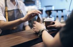 Young woman or barista serving customer at coffee shop.Takeaway. And service concept, Small Business. Owner Business Stock Photography