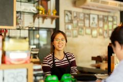 Young woman barista serving customer with smile face at counter bar in cafe. stock photos