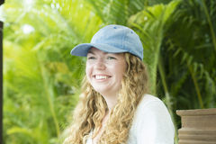 Young Woman in Basball Cat Smiling in Mexico. Beautiful, Blond, Young Woman in Basball Cat Smiling with Dense Vegetation in the Backgound. Mexico Stock Images