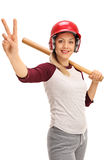 Young woman with a baseball bat and a helmet making a peace sign Royalty Free Stock Photography