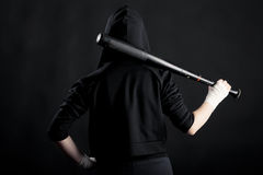 Young woman with a baseball bat. View from the back. hoodlum. Young woman with a baseball bat. View from the back. street hoodlum Stock Photos