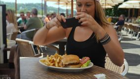 Young Woman in Baseball Hat Photos Her Meal at Outdoor Restaurant. A young millennial takes a picture of her lunch then posts on social media. Outside restaurant stock footage