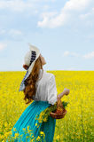 Young woman with basket at canola field Royalty Free Stock Photography