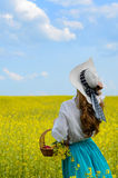 Young woman with basket at canola field Stock Photo