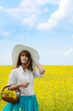 Young woman with basket at canola field Royalty Free Stock Photos