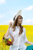 Young woman with basket at canola field Royalty Free Stock Photo