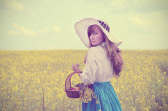 Young woman with basket at canola field Royalty Free Stock Image