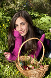 Young woman with basket of eggs picking flowers Stock Photos