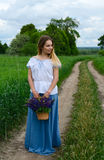 Young woman with basket of meadow flowers on rural road. Beautiful young woman stands with basket of wild flowers on rural road Stock Images